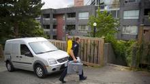 New Westminster Police and forensic teams examine the apartment complex of 211 Eleventh Street in New Westminster on Tuesday. Two escorts where found dead in their apartments this month. (Ben Nelms/The Globe & Mail)