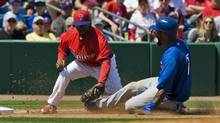 Philadelphia Phillies infielder Jimmy Rollins (L) tags out Toronto Blue Jays baserunner Jose Reyes (R) at third base during the fifth inning of their MLB spring training baseball game in Clearwater, Florida, March 28, 2013. (STEVE NESIUS/REUTERS)