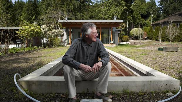 Architect Peter Pratt sits outside the home he designed, which sits to the right of his father's original 1953 home. (Rafal Gerszak For The Globe and Mail)
