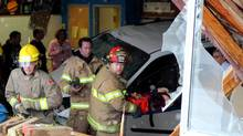 Rescue workers respond to a scene where a vehicle crashed into classroom in St. Paul, Alberta, Thursday, October 25, 2010. (Ryan McCracken/St. Paul Journal)
