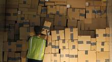 A worker stacks a shipping trailer with boxed items for delivery at Amazon's distribution centre in Phoenix. (RALPH FRESO/REUTERS)
