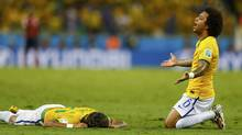 Brazil's Marcelo (R) reacts next to teammate Neymar after Neymar was injured in a challenge against Colombia during their 2014 World Cup quarter-finals at the Castelao arena in Fortaleza July 4, 2014. (Marcelo Del Pozo/REUTERS)