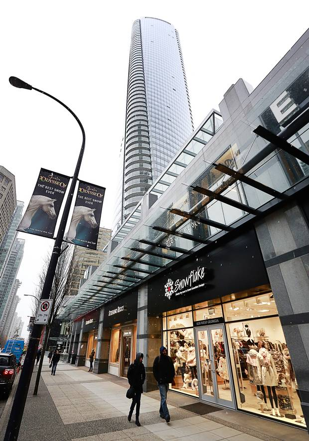 Pedestrians walk past a store situated in the retail space outside the Trump International Tower and Hotel in Vancouver.