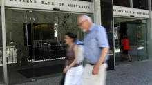 People walk past the Reserve Bank of Australia building in Sydney, Tuesday, Dec. 4, 2012. The Reserve Bank of Australia's decision to lower the rate to 3 per cent marked the bank's fourth rate cut this year and was widely predicted by economists. (Rick Rycroft/AP)