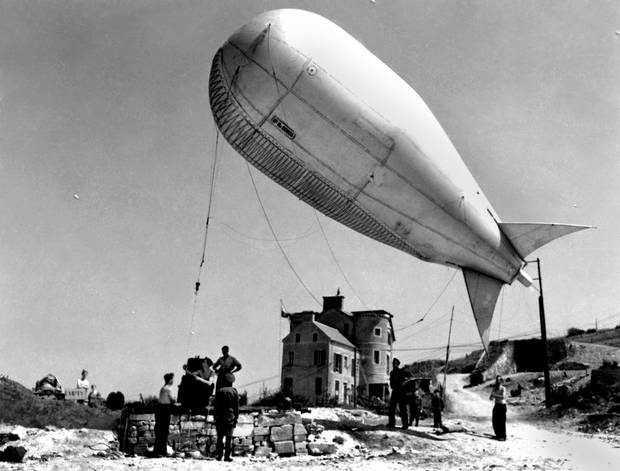 A tethered barrage balloon is deployed to ward German planes away from Allied ships unloading troops and supplies in Normandy.