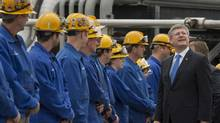 Prime Minister Stephen Harper looks around as he chats with workers during a visit to the Irving Oil refinery in Saint John, N.B. on Thursday, Aug. 8, 2013. (Andrew Vaughan/THE CANADIAN PRESS)