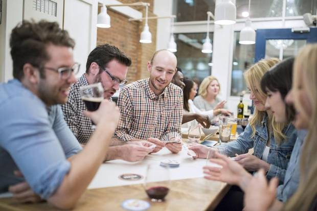 Friends socialize over drinks and appetizers at the Boxcar Cafe, a newly opened board game cafe in downtown Calgary.