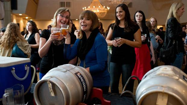 Laura MacDonald, left, and Yvonne Gettins try one of the local brews available at an event put on by the Society of Beer Drinking Ladies in Toronto, Sept. 30.