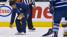 A member of the ice crew picks up waffles tossed on the ice on Dec. 20 during a game against the Atlanta Thrashers. (Nathan Denette/The Canadian Press)