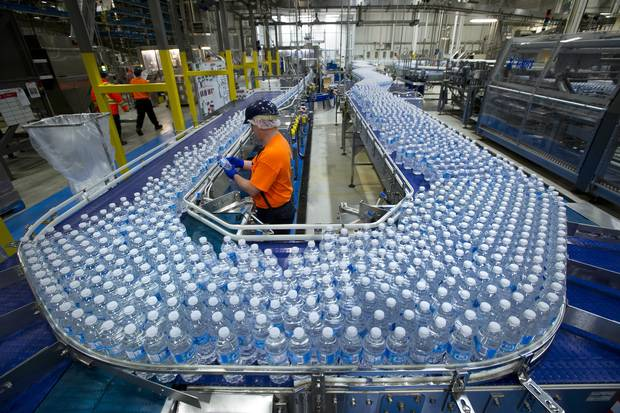 A worker inspects bottles of water at the Nestlé Waters Canada plant near Guelph, Ont., on Jan. 16, 2015.
