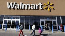 In this Feb. 20, 2012, file photo, customers walk into and out of a Wal-Mart store in Methuen, Mass. (Elise Amendola/AP)