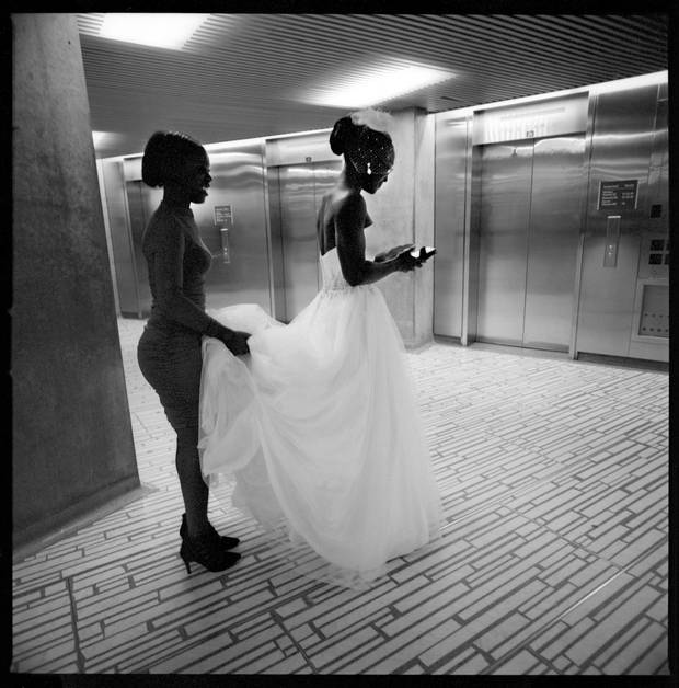 Alexis Clayton-Smith holds the train to her sister Charmaine Smith's wedding gown while waiting for an elevator that will take them to the third-floor chapel at Toronto City Hall.