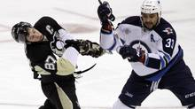 In this file photo, Pittsburgh Penguins' Sidney Crosby (87) gets a high stick from Winnipeg Jets' Dustin Byfuglien (33) in the first period of an NHL hockey game in Pittsburgh Tuesday, March 20, 2012. On Saturday, The NHL has reversed course and will not review high-sticking penalties this season, league executive vice-president and director of hockey operations Colin Campbell said. (GENE J. PUSKAR/AP)