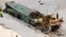 A piece of heavy equipment strains to move a bus which plummeted 200 feet down an embankment in rural Eastern Oregon on Dec. 30, 2012, killing nine and sending multiple people to hospital. (RANDY L. RASMUSSEN/THE CANADIAN PRESS)