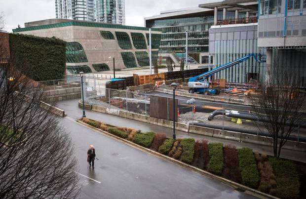 A woman walks towards Surrey Central SkyTrain station from Surrey city hall.