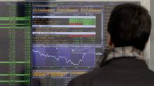 A man checks stock indexes on a screen of a bank in Milan, Italy, Monday, Nov. 28, 2011. (Luca Bruno/AP)