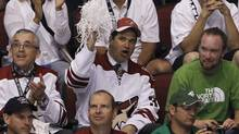 Chicago businessman Matthew Hulsizer, middle, who is trying to buy the Phoenix Coyotes, cheers on the team during the second period in Game 4. (Ross D. Franklin/Associated Press)