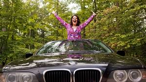 Opera singer Sondra Radvanovsky pops out of the sunroof in her 2002 BMW station wagon.