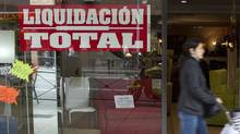 A woman passes a shop with a closing sale in Madrid, April 27, 2012 (SERGIO PEREZ)