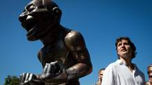 "Liberal leader Justin Trudeau stops to look at Chinese artist Yue Minjun's ""A-mazing Laughter"" statues while on his way to a meet and greet with people on the street near English Bay in Vancouver, B.C., on Thursday July 25, 2013. (DARRYL DYCK For The Globe and Mail)"