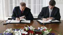 Michael Ambuehl of the Swiss finance department, left, and Donald Sternoff Beyer, U.S. ambassador to Switzerland, sign the Foreign Account Tax Compliance Act in Bern Feb. 14, 2013. (PASCAL LAUENER/REUTERS)
