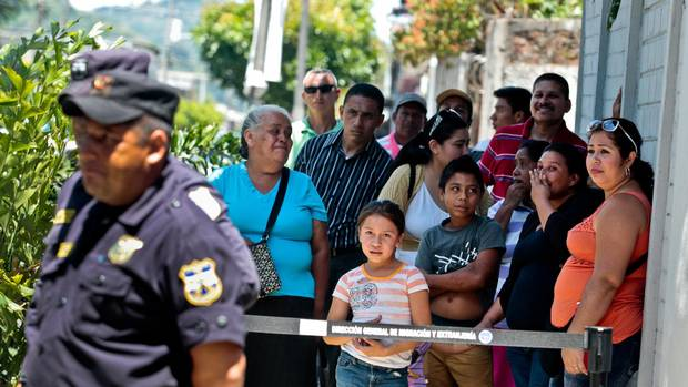 Relatives wait as a bus arrives with a group of children being sent back from Mexico at the Care Center for Migrants in Santa Tecla, El Salvador.