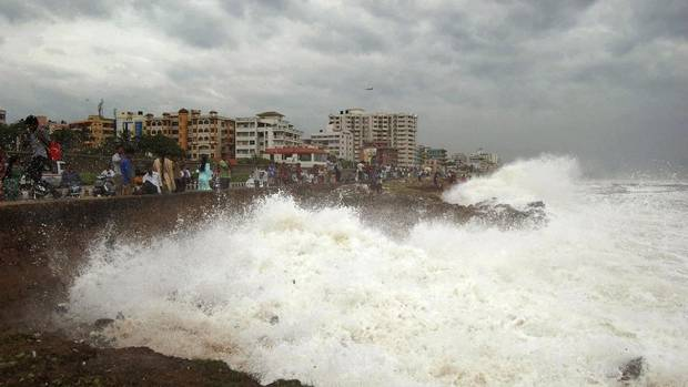 People in eastern India watch high tide waves as they stand at the Bay of Bengal coast in Vishakhapatnam, India, Saturday, Oct. 12, 2013. (THE ASSOCIATED PRESS)