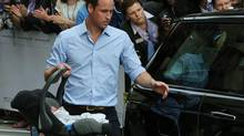 Britain's Prince William, carries the Prince of Cambridge to the car, Tuesday July 23, 2013, as they leave St. Mary's Hospital exclusive Lindo Wing in London where the Duchess gave birth on Monday July 22. The Royal couple are expected to head to London's Kensington Palace from the hospital with their newly born son, the third in line to the British throne. (Joel Ryan/AP)