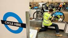 Workers in London attach branding stickers and signs to bicycles for London's new rent-a-bike program. (Oli Scarff/Getty Images)