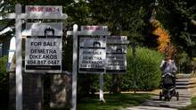 A woman walks past homes for sale in the Kitsilano neighborhood in Vancouver, B.C., in September, 2012. Royal LePage expects Canadian house prices to remain soft until mid-2014. (Darryl Dyck For The Globe and Mail)