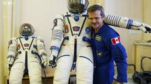 The International Space Station (ISS) crew member Canadian astronaut Chris Hadfield holds his suit during a training at Baikonur cosmodrome December 7, 2012. Hadfield with his crewmates Russian cosmonaut Roman Romanenko and U.S. astronaut Thomas Marshburn is scheduled to fly to the International Space Station on December 19. (SERGEI REMEZOV/REUTERS)
