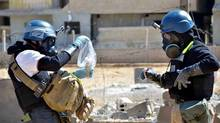 In this Wednesday, Aug. 28, 2013 citizen journalism image provided by the United media office of Arbeen which has been authenticated based on its contents and other AP reporting, members of the UN investigation team take samples from sand near a part of a missile that is likely to be one of the chemical rockets according to activists, in the Damascus countryside of Ain Terma, Syria. Russia's proposal to place Syria's chemical weapons stockpile under international control for dismantling would involve a lengthy and complicated operation made more difficult by a deep lack of trust. Syria is believed by experts to have 1,000 tons of chemical warfare agents scattered over several dozen sites across the country, and just getting them transferred while fighting rages presents a logistical and security nightmare. (AP)