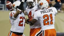 BC Lions' Adam Bighill (44), J.R. LaRose (27) and Ryan Phillips (21) celebrate Bighill's touchdown after recovering Winnipeg Blue Bombers' fumble on their first play of the game in the first half of CFL action in Winnipeg Friday, September 27, 2013. (JOHN WOODS/THE CANADIAN PRESS)