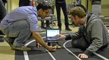 McMaster engineering students make changes to the software code that controls their robot car . (Peter Cheney/The Globe and Mail)