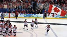 Roberto Luongo carries the flag Dave Ash brought to the gold-medal game during the medals ceremony in men's ice hockey at Canada Hockey Place during the XXI Winter Olympic Games in Vancouver. (CRIS BOURONCLE/AFP/Getty Images)