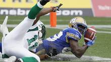Winnipeg Blue Bombers' Clarence Denmark (89) snags a pass in the endzone in front of Saskatchewan Roughriders' Carlos Thomas (11) during the first half of their CFL game in Winnipeg Sunday, September 8, 2013. The touchdown was disallowed. (John Woods/THE CANADIAN PRESS)