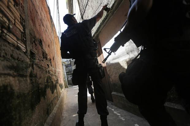 Officers patrol in the Babilonia favela community, which stands on a hillside above Copacabana beach, an Olympic venue site, in Rio de Janeiro on July 26, 2016.