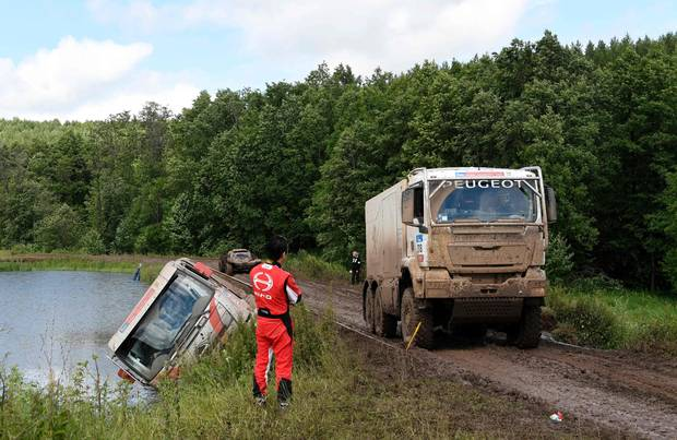 Japanese truck driver Teruhito Sugawara and co-driver Hiroyuki Sugura stand next to a vehicle which fell off a road in the Stage 2 of the Silk Way 2017 between Tcheboksary and Ufa, Russia, on July 9, 2017.