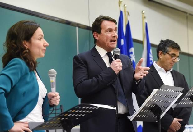 Pierre-Karl Peladeau, middle, attends a Parti Québécois debate with candidates Martine Ouellet, left, and Pierre Céré at Quebec City's Laval campus on March 18, 2015.
