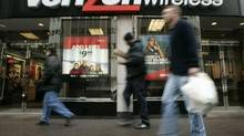 Pedestrians walk past a Verizon Wireless shop in Washington in this file photo. Moody's says a price war is unlikely if a big foreign player enters Canada's wireless market. (CHARLES DHARAPAK/AP)