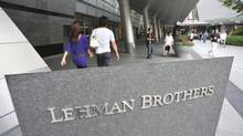 People stroll by a company sign of troubled firm Lehman Brothers Holdings Inc. (Katsumi Kasahara/The Associated Press)