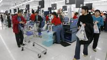 Shoppers at a Wal-Mart store in Beijing. Lowering taxes for the poor and consumers will make China's people feel richer, and spend more. (CLARO CORTES IV/Reuters)