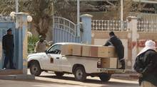 Workers deliver empty coffins to collect the bodies of hostages killed at the In Amenas gas plant in Algeria. (REUTERS)