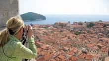 A tourist photographs the red tile roofs of Dubrovnik, Croatia. The ancient walled city is a popular stop for cruise ships in the Mediterranean (Randall Moore/Randall Moore/The Globe and Mail)