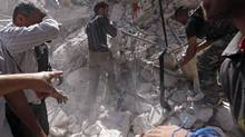 Civilians and members of the Free Syrian Army try to pull out a body from under the rubble of a building destroyed by a jet air strike in al-Kalaseh neighbourhood in Aleppo September 19, 2012. (ZAIN KARAM/REUTERS)