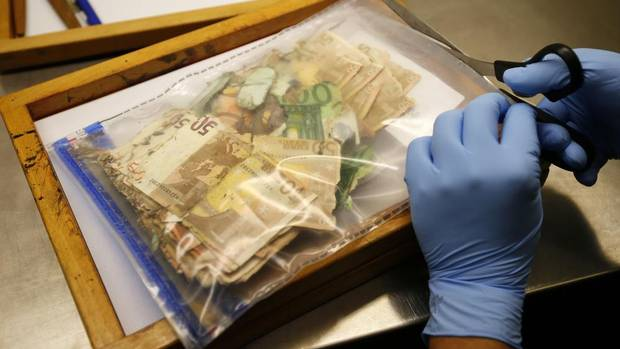 A forensic scientist opens a plastic pack containing euro banknotes which were damaged during the recent floods, at the money analyzing laboratory of Germany's Federal Reserve bank, Deutsche Bundesbank, in Mainz, July 31, 2013. The 13-member analyzing team specialize in the reconstruction of damaged or destroyed banknotes. Once the banknotes are verified, the Bundesbank will transfer the money back to the owner's account, while the damaged notes will be burned. (KAI PFAFFENBACH/REUTERS)