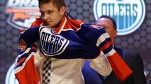 Leon Draisaitl puts on a team sweater after being selected as the number three overall pick to the Edmonton Oilers in the first round of the 2014 NHL Draft at Wells Fargo Center. (Bill Streicher/USA Today Sports)