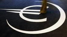 A woman walks on the symbol for the euro during the inauguration of an exhibition on the 10th anniversary of the currency in Lisbon (NACHO DOCE)