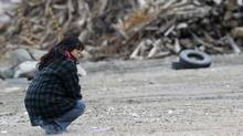 A woman kneels near a pile of debris while offering prayers in the earthquake and tsunami devastated city of Rikuzentakata, Iwate prefecture, northeastern Japan, Sunday, March 11, 2012. (Koji Sasahara/AP/Koji Sasahara/AP)