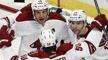 Phoenix Coyotes left wing Taylor Pyatt (14) celebrates his third period goal against the Chicago Blackhawks with his teammates Keith Yandle (L), Radim Vrbata (R) and Antoine Vermette (50) during Game 4 of their NHL Western Conference quarter-final hockey playoffs in Chicago, Illinois April 19, 2012. REUTERS/Jim Young (Jim Young/Reuters)